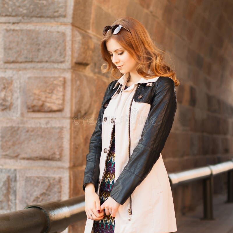 Ritratto della primavera di bella ragazza in un cappotto ed in un vestito Interim fotografia stock libera da diritti