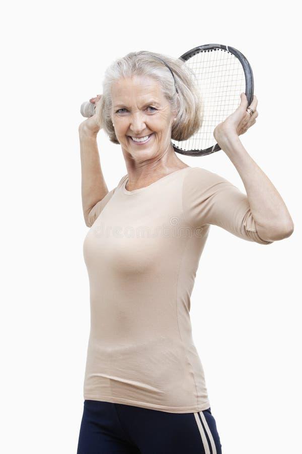 Ritratto della racchetta di tennis senior della tenuta della donna sopra la sua spalla contro fondo bianco immagini stock libere da diritti