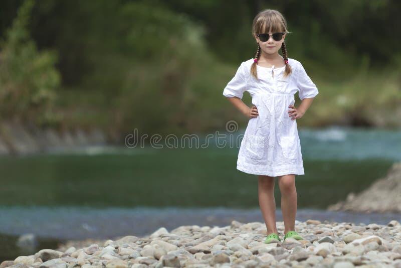 Ritratto della ragazza abbastanza divertente sveglia con le trecce bionde in vestito bianco ed occhiali da sole scuri fotografie stock