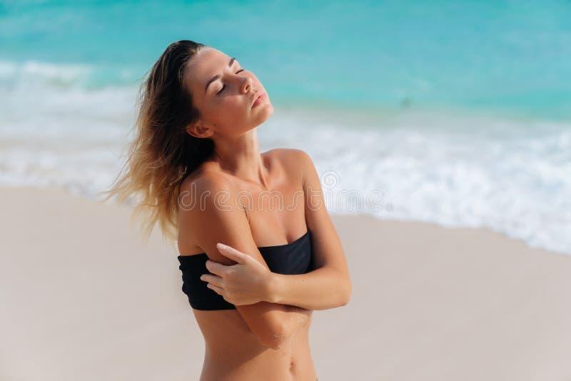 Ritratto della ragazza abbronzata sensuale in costume da bagno nero sulla spiaggia sabbiosa immagini stock libere da diritti
