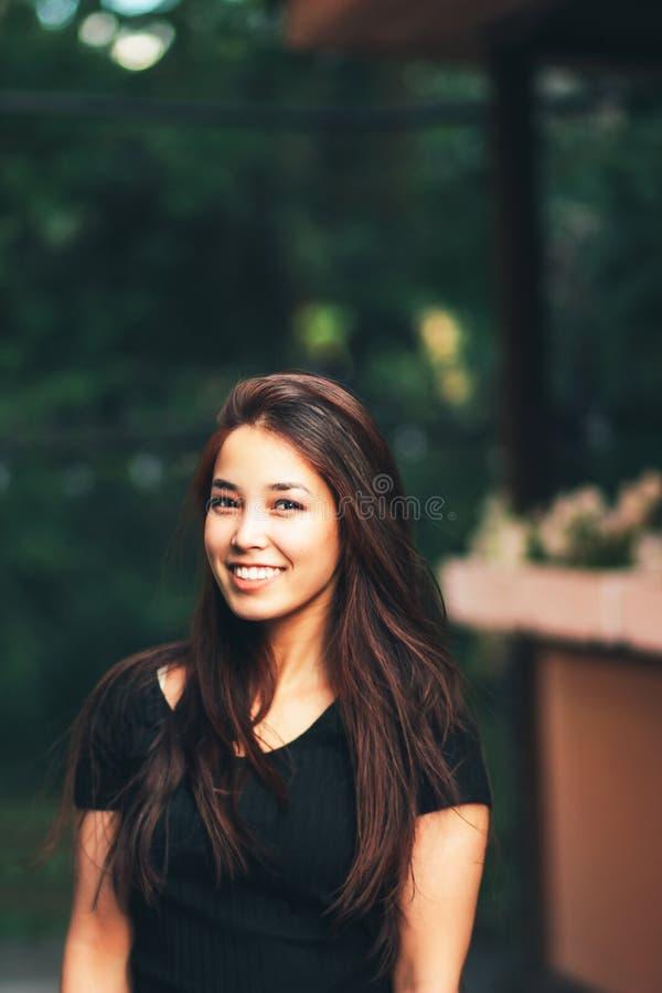 Ritratto della ragazza asiatica dei bei capelli lunghi felici in maglietta nera sulla via fotografia stock libera da diritti