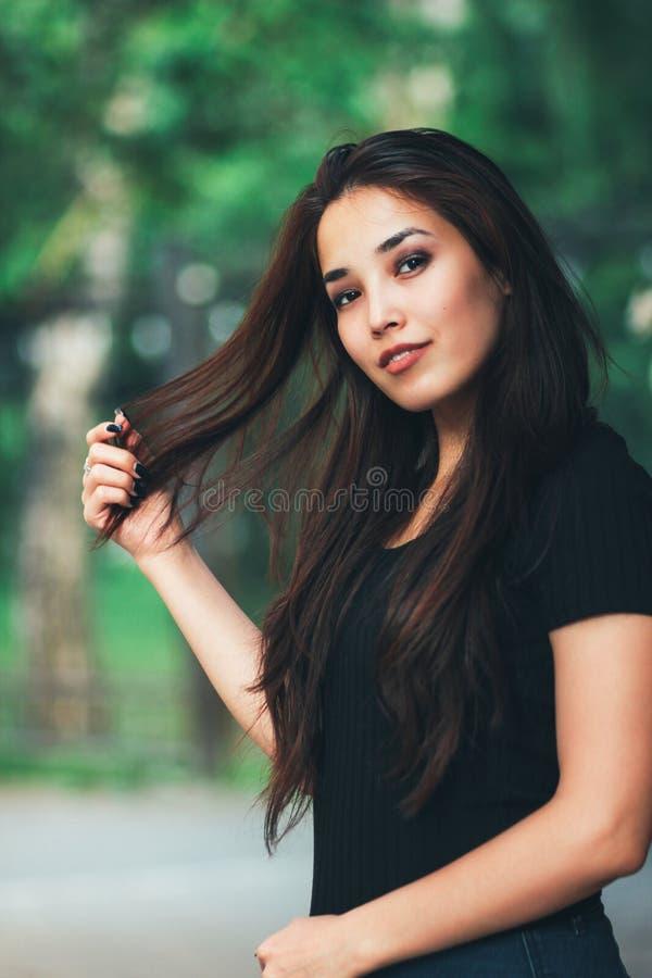 Ritratto della ragazza asiatica dei bei capelli lunghi felici in maglietta nera sulla via fotografie stock libere da diritti