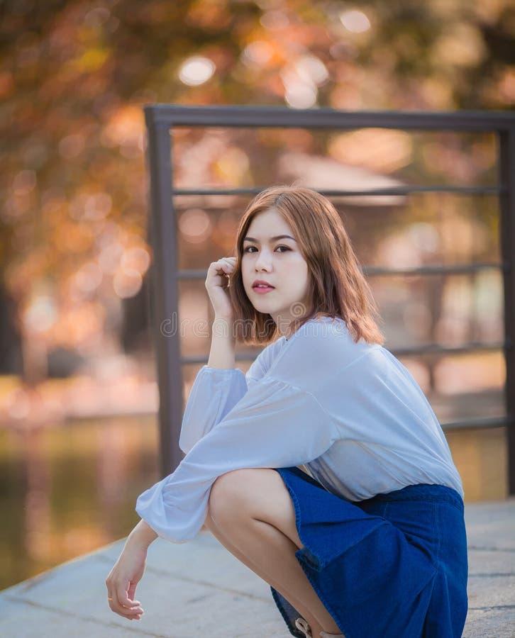 Ritratto della ragazza asiatica dei giovani pantaloni a vita bassa che posa nei precedenti della foresta del parco del autume fotografia stock libera da diritti
