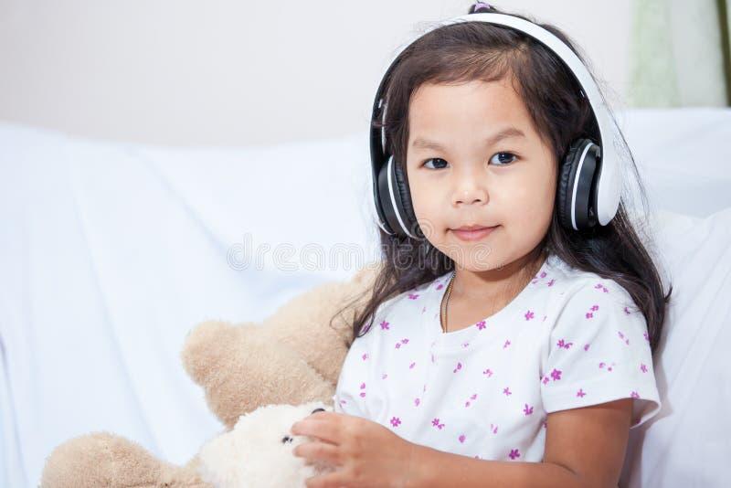 Ritratto della ragazza asiatica sveglia del bambino che ascolta la musica fotografie stock libere da diritti