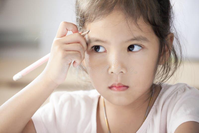 Ritratto della ragazza asiatica sveglia del bambino che pensa e che disegna immagine stock