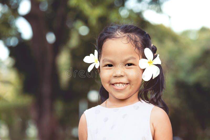 Ritratto della ragazza asiatica sveglia del bambino con il fiore sulle sue orecchie fotografie stock libere da diritti