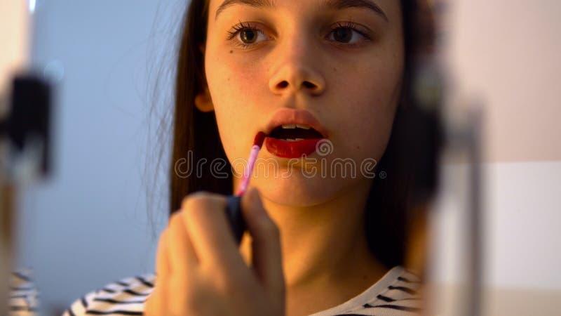 Ritratto della ragazza attraente che rouging le sue labbra immagine stock