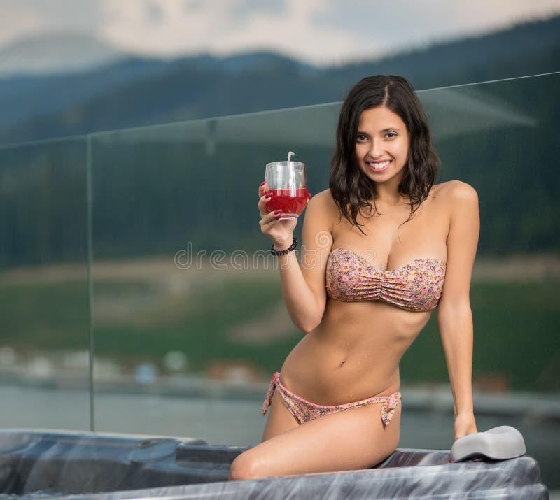 Ritratto della ragazza attraente felice con l'ente perfetto in bikini che si siede alla Jacuzzi con il cocktail fotografia stock