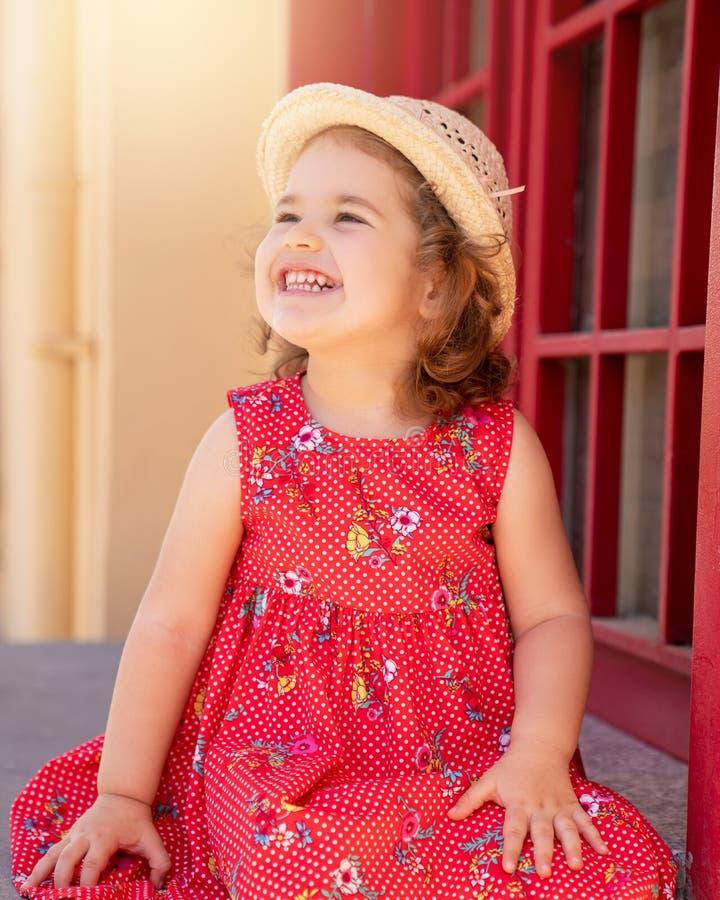 Ritratto della ragazza bionda sveglia in abbigliamento che posa in Sunny Day e che esamina la macchina fotografica l'aria aperta fotografia stock