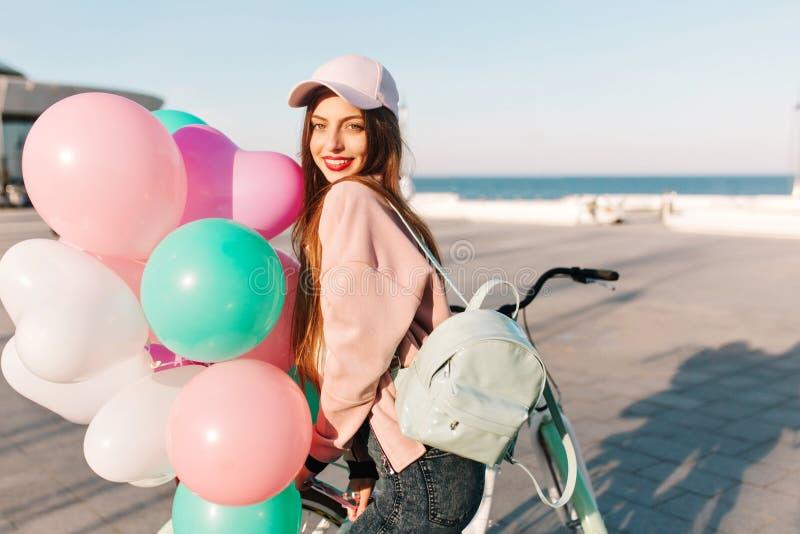 Ritratto della ragazza castana sorridente adorabile in cappuccio rosa d'avanguardia con lo zaino che cammina lungo il pilastro de fotografia stock libera da diritti
