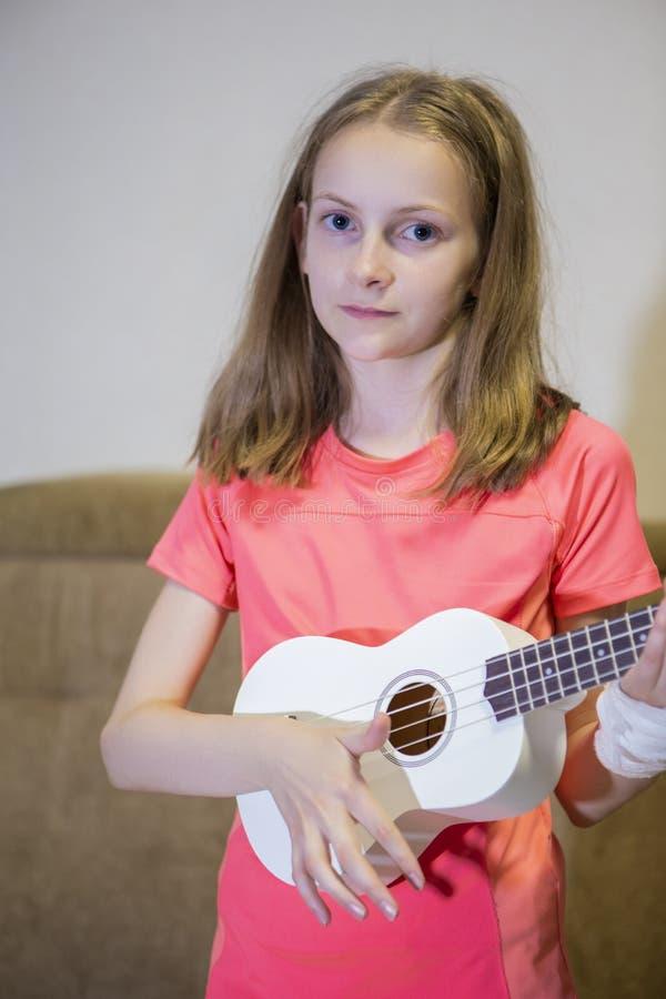 Ritratto della ragazza caucasica con la mano danneggiata in gesso Posando con la piccola chitarra all'interno immagini stock libere da diritti