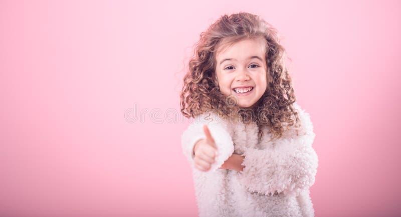 Ritratto della ragazza che indica dito su sopra al rosa immagini stock libere da diritti