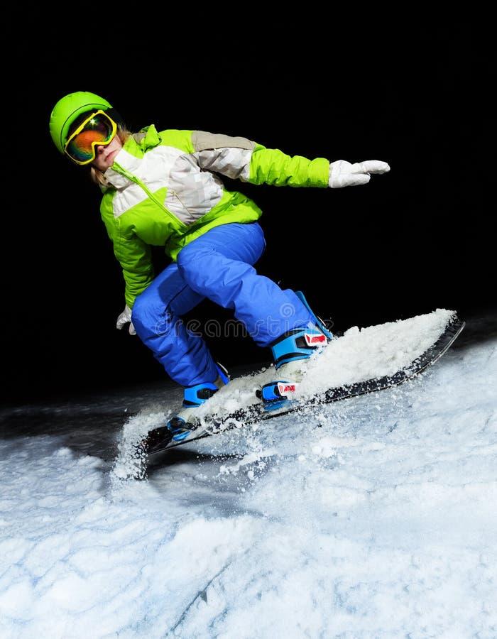 Ritratto della ragazza che salta sullo snowboard alla notte immagine stock libera da diritti