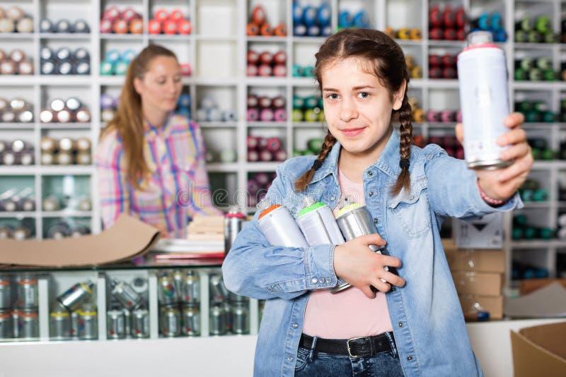 Ritratto della ragazza che sceglie colore della pittura in bomboletta spray in sho di arte fotografie stock libere da diritti