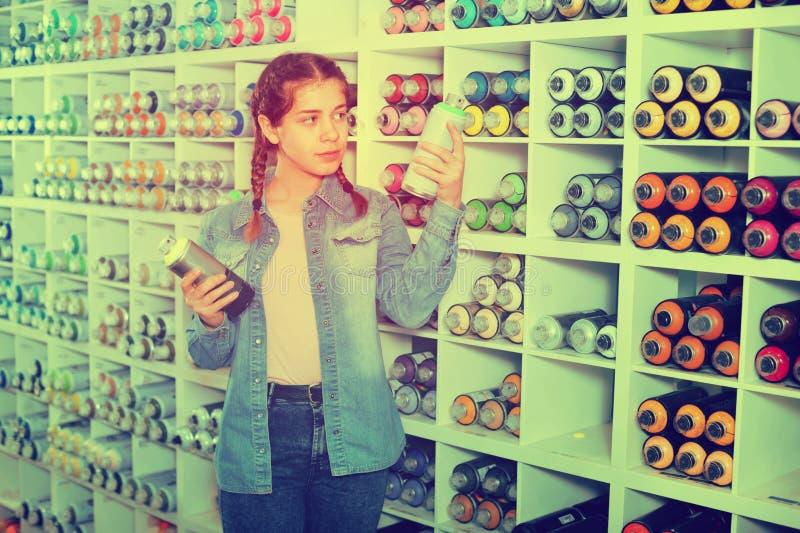 Ritratto della ragazza che sceglie colore della pittura in bomboletta spray in sho di arte immagine stock
