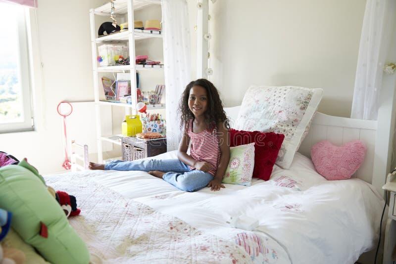 Ritratto della ragazza che si siede sul letto in camera da letto immagini stock