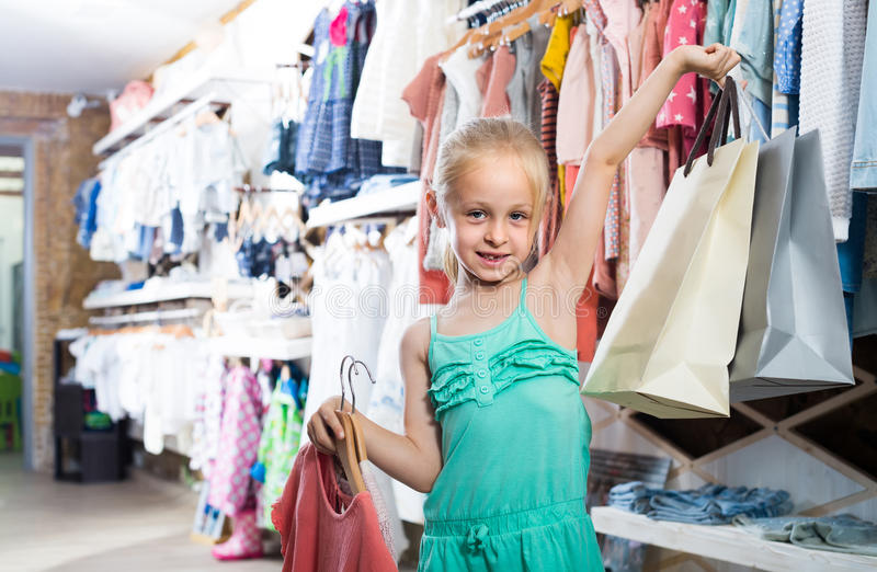 Ritratto della ragazza che sta nel deposito dei vestiti dei bambini con la b di compera fotografia stock