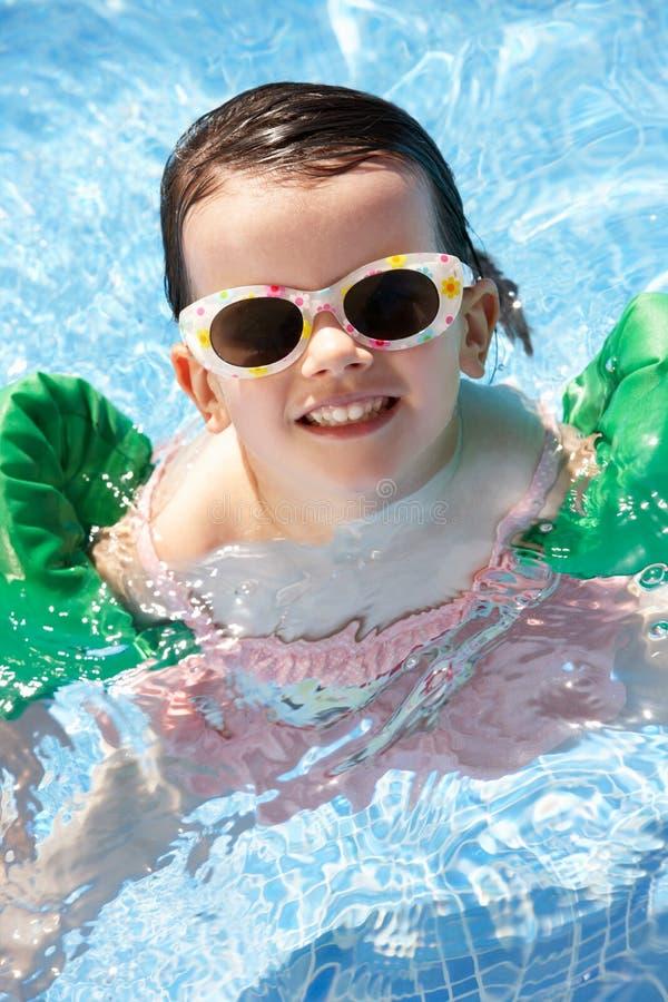 Ritratto della ragazza con i bracciali nella piscina fotografia stock libera da diritti