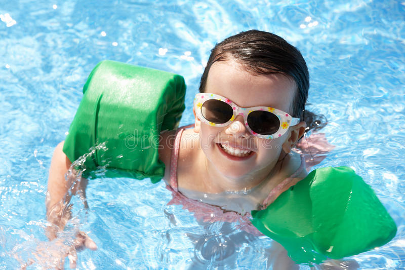 Ritratto della ragazza con i bracciali nella piscina fotografia stock
