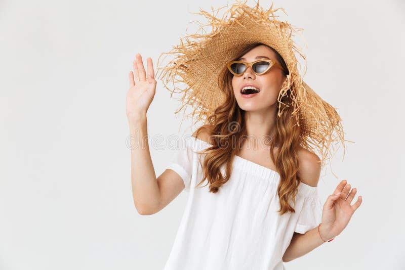 Ritratto della ragazza contenta alla moda 20s che indossa il grande cappello di paglia e s fotografia stock