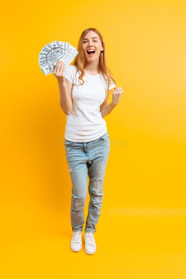 Ritratto della ragazza contenta felice con un mazzo di banconote e di vittoria di celebrazione e un successo sopra fondo giallo fotografia stock