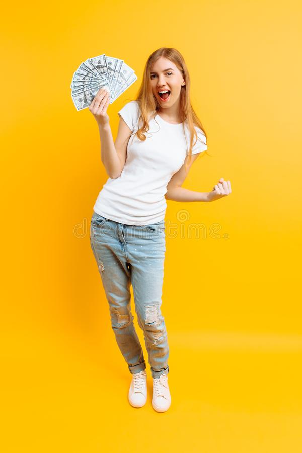 Ritratto della ragazza contenta felice con un mazzo di banconote e di vittoria di celebrazione e un successo sopra fondo giallo fotografia stock libera da diritti