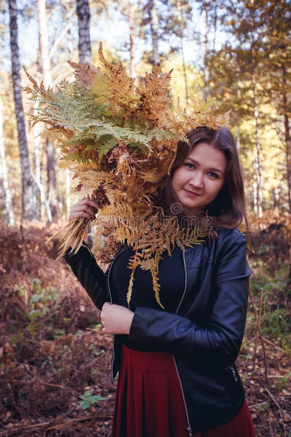 Ritratto della ragazza dai capelli marrone con un mazzo della felce gialla nella foresta, concetto di caduta di autunno nel parco immagini stock libere da diritti