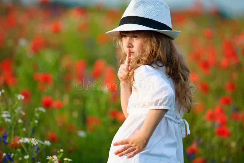 Ritratto della ragazza del bambino che fa un gesto di silenzio con il dito sulle labbra immagine stock