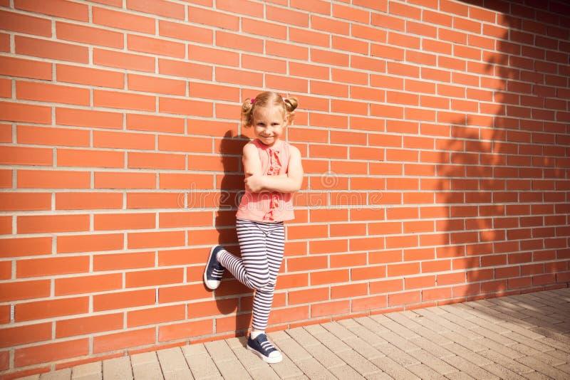 Ritratto della ragazza del bambino che ride del fondo della parete di mattoni immagine stock