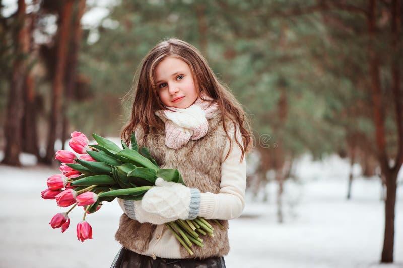 Ritratto della ragazza del bambino con i fiori sulla passeggiata all'aperto calda accogliente di inverno fotografia stock libera da diritti