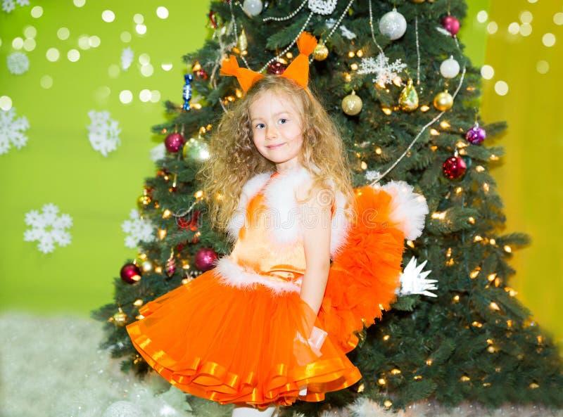 Ritratto della ragazza del bambino negli scoiattoli di un vestito intorno ad un albero di Natale decorato Bambino sul nuovo anno  immagine stock libera da diritti