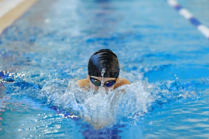 Ritratto della ragazza del primo piano in occhiali di protezione e dello stile del colpo di farfalla di nuoto del cappuccio nello fotografie stock libere da diritti