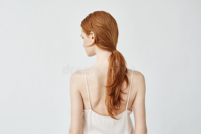 Ritratto della ragazza della testarossa che posa il fronte posteriore di tornitura alla macchina fotografica fotografie stock