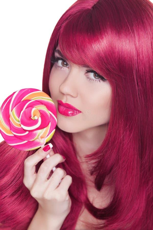 Ritratto della ragazza di bellezza che tiene lecca-lecca variopinta. Trucco di fascino. fotografia stock libera da diritti