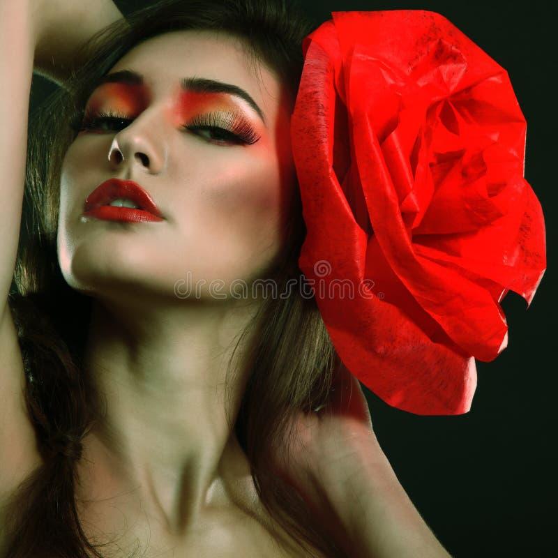 Ritratto della ragazza di fascino di modo con il fiore rosso in suoi capelli fotografia stock