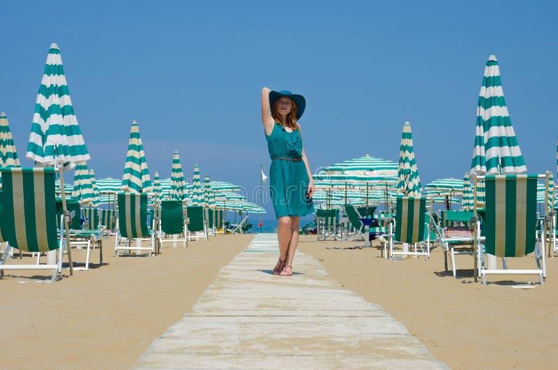 Ritratto della ragazza diritta in cappello sul percorso della spiaggia immagini stock libere da diritti