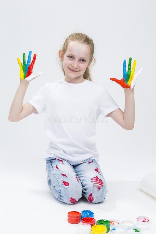 Ritratto della ragazza divertente che mostra le mani variopinte sudicie dipinte brillantemente fotografia stock libera da diritti