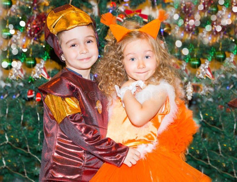 Ritratto della ragazza e del ragazzo del bambino negli scoiattoli di un vestito intorno ad un albero di Natale decorato Bambini s immagini stock libere da diritti
