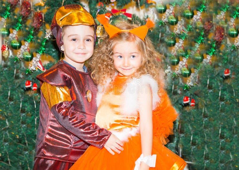 Ritratto della ragazza e del ragazzo del bambino negli scoiattoli di un vestito intorno ad un albero di Natale decorato Bambini s immagine stock