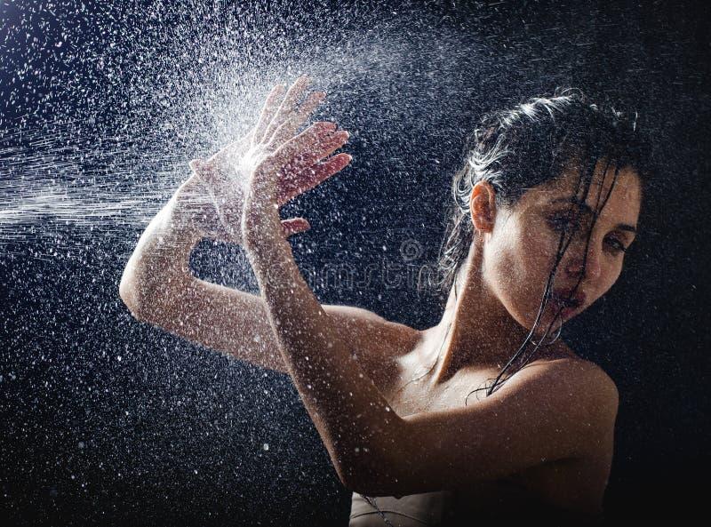 Ritratto della ragazza ed acqua di spruzzatura nel suo fronte bello modello femminile su fondo nero fotografie stock libere da diritti