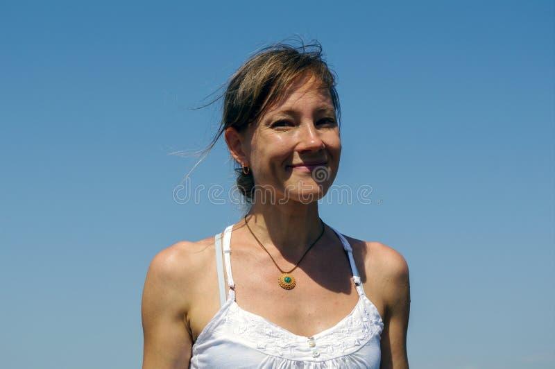 Ritratto della ragazza felice alla moda con fondo blu fotografia stock