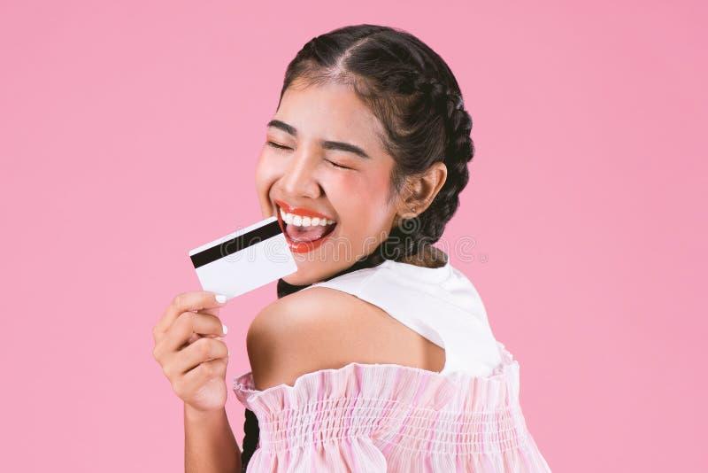 Ritratto della ragazza felice che mostra la carta di credito sopra backg rosa fotografie stock libere da diritti