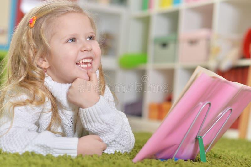 Ritratto della ragazza felice sveglia che studia a casa immagini stock