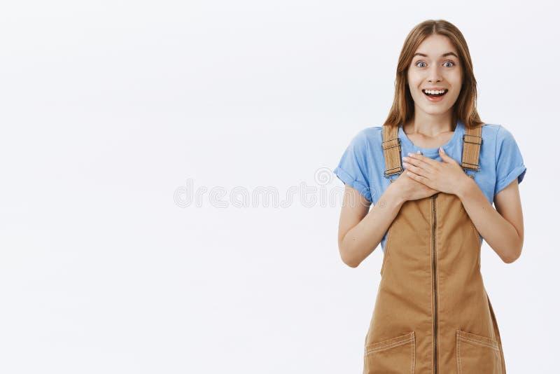 Ritratto della ragazza gentile affascinante riconoscente contentissima in camici marroni che giudicano le palme urgenti al petto  immagini stock
