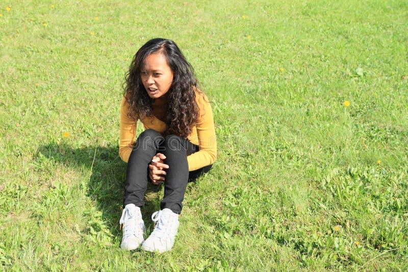 Ritratto della ragazza graziosa che si siede sull'erba fotografia stock libera da diritti