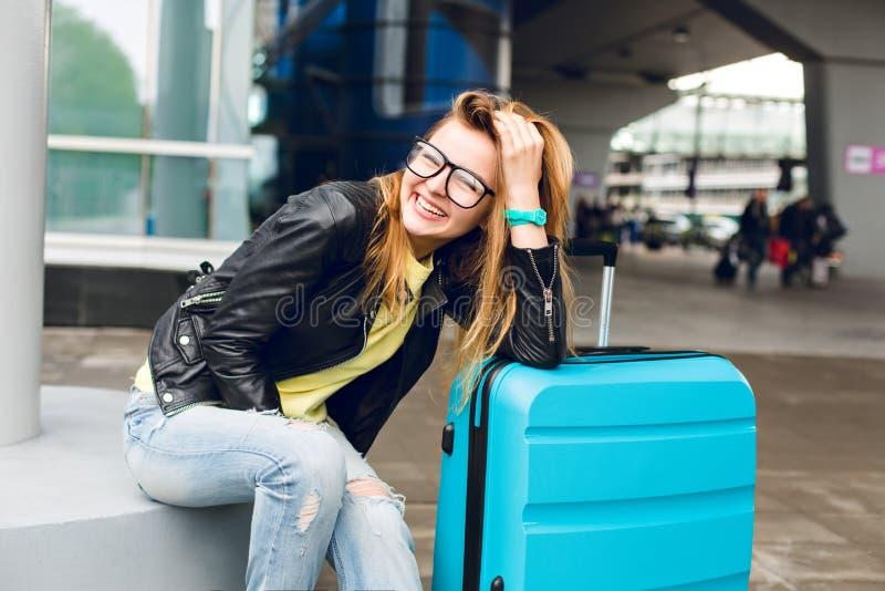 Ritratto della ragazza graziosa con capelli lunghi in vetri che si siedono fuori nell'aeroporto Porta il maglione giallo con il r fotografia stock libera da diritti