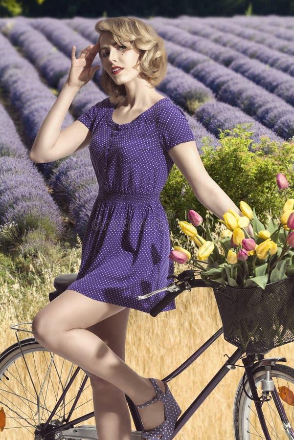 Ritratto della ragazza graziosa con la bicicletta. lavander all'aperto del campo immagini stock libere da diritti