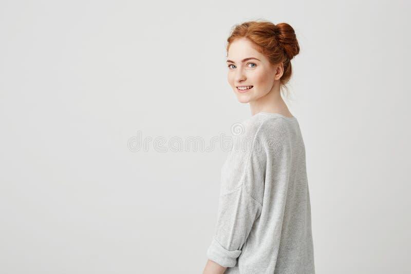Ritratto della ragazza graziosa felice allegra della testarossa che sorride esaminando macchina fotografica sopra fondo bianco fotografie stock libere da diritti