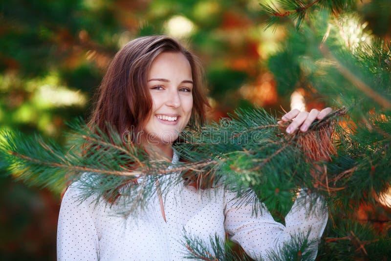 Ritratto della ragazza graziosa sorridente nei rami attillati verdi fotografia stock libera da diritti