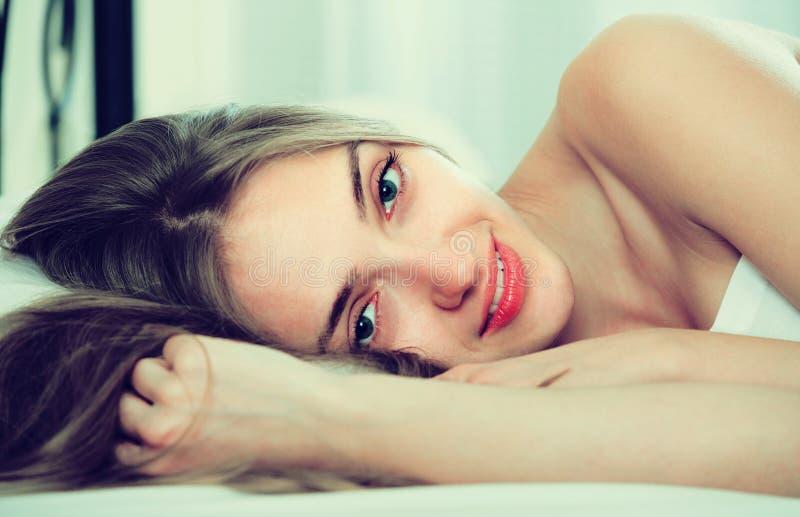Ritratto della ragazza graziosa sveglio a letto fotografia stock